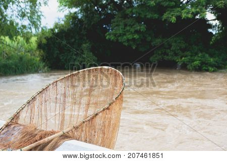 Swing net shape spoon for fishing fishing net with the river and trees background.