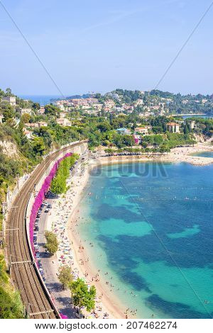 Beautiful daylight view from top of mountains to luxury resort villefranche sur mer and bay on french riviera at mediterranean sea Cote d'Azur in France. Railways and beach with people