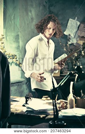 Writer at work. Handsome young writer standing near the table and making up something in his mind at home
