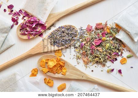 various herbal tea ingredients in wooden spoons with tea bags over white wooden background