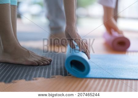 Yoga practitioner folding yoga mat after class at studio. Workout lifestyle for meditation body balance vs body strength. Yoga mat is equipment support practitioner during workout. Healthcare concept