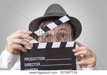 Actress with movie clapper behind face close up image.