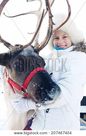 Happy little girl hugging her reindeer. Winter playtime.