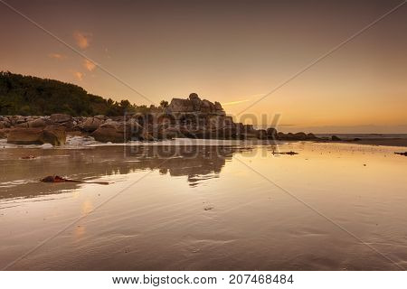 Sunset behind ancient customs house in the rocks above the beach of Kerfissien, Finistere, France