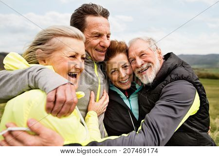 Group of active senior runners outdoors, resting and hugging in windy cold weather.