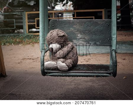 Miserable wet Teddy bear on a swing in the rain