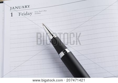 Metal pen on a calendar with the page showing the first day of the year in a setting goals concept