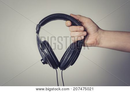 Black headphones in hand. Concept of entertainment.