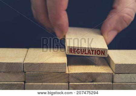 Regulation word written on wooden block. Business concept.