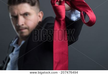 annoyed businessman terminate the job and take off the red tie