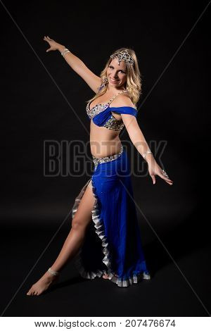 Beautiful belly dancer performing belly dance on black background.