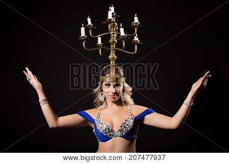 Beautiful belly dancer performing belly dance with candle holder on black background.
