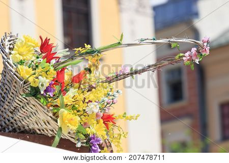 Beautiful bouquet of yellow flowers in wicker brown basket on sity background