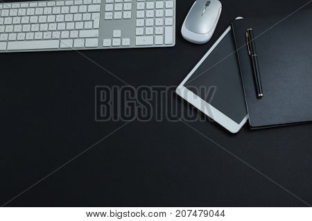 Overhead of keyboard, mouse, digital tablet, pen and organizer on black background