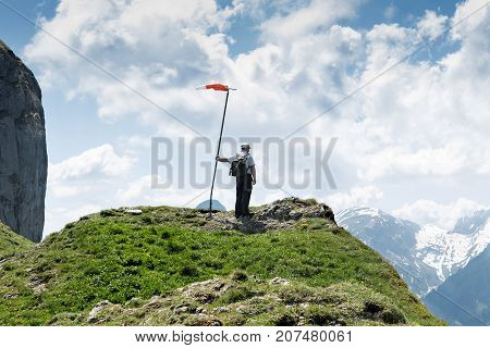 hiker standing next to the wind vane and looking down to the valley