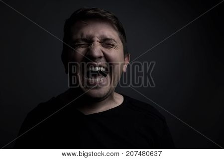portrait of man yell of pain in front of grey background