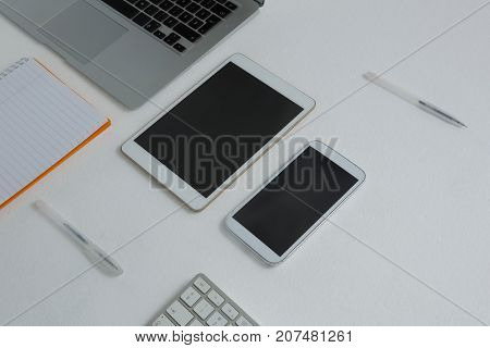 Overhead of various electronic gadgets and book on white background