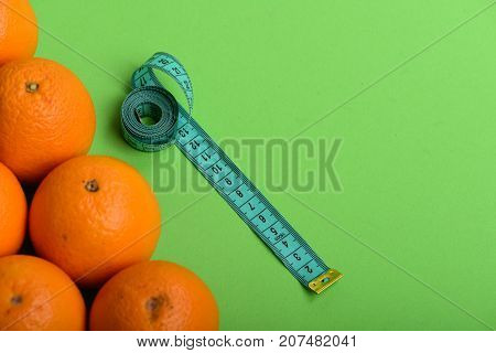Oranges Near Long Measuring Tape On Green Background, Top View