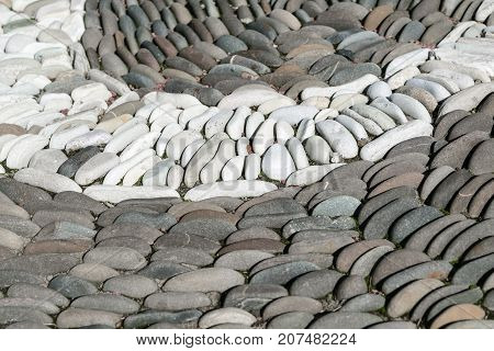 White oval stones stacked arch or semi-circle among the dark stones. The stones are located one behind the other in several rows. Between the stones are small leaves.