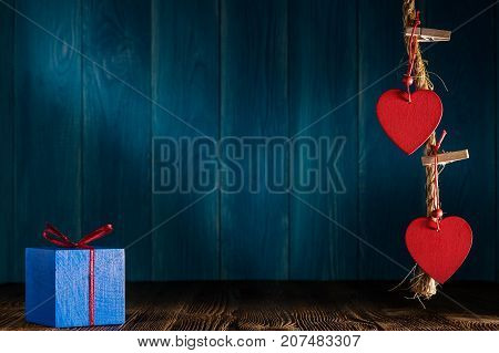 Red wooden hearts on the twine with clothespins and gift box on blue wooden background. Valentine's Day cards with copy space. Romance love concept.