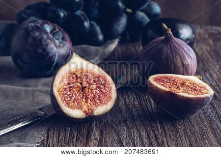 Still life with figs. The fig is cut into halves on a wooden table. Photo toned