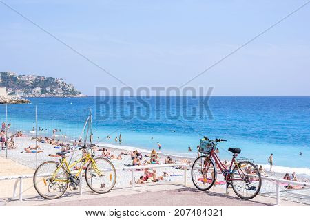 NICE COTE D'AZUR, FRANCE - JUNE 27,2017: Beautiful daylight view to city blue sea. People walking and relaxing on beach. Two bycicles parked on ground.
