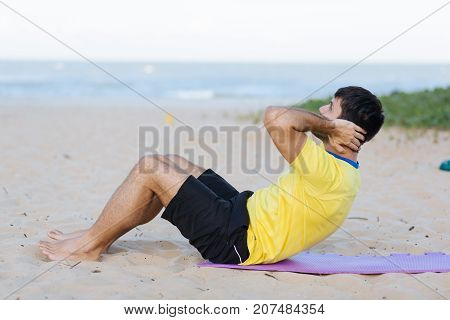 Sports And Healthy Lifestyle. Young Man Doing Crunches On The Ocean Beach