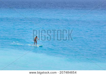 NICE COTE D'AZUR, FRANCE - JUNE 27,2017: Beautiful daylight view to beach in France. Blue water and a man surfing.