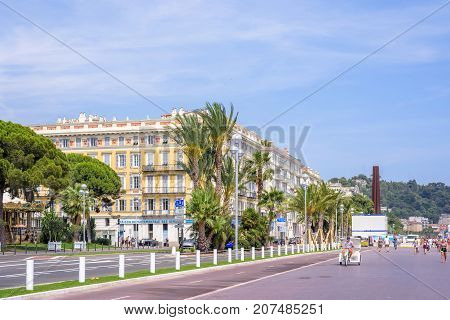 NICE COTE D'AZUR, FRANCE - JUNE 27, 2017: Beautiful daylight view to city streets and beautiful yellow buildings. People walking on sidewalk