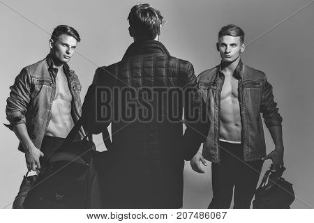 men or photographer with naked torso and sexy body holds photo camera and bags black and white