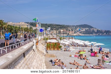 NICE COTE D'AZUR, FRANCE - JUNE 27,2017: Beautiful daylight view to beach resort. Blue water with people walking on sand and sidewalk.