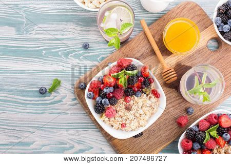 Top view of diet food for breakfast. Oatmeal, fresh berries, honey and a refreshing vitamin drink. light table. copy space