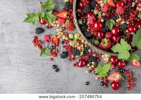 Top view of assorted ripe berries in a plate on a stone background. Copy space.