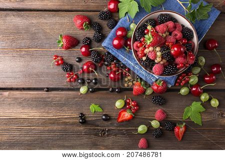 Top view of assorted ripe berries in a plate on a wooden background. Copy space.
