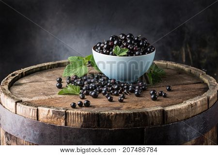 Black currant in a blue bowl on a wooden board on a dark background