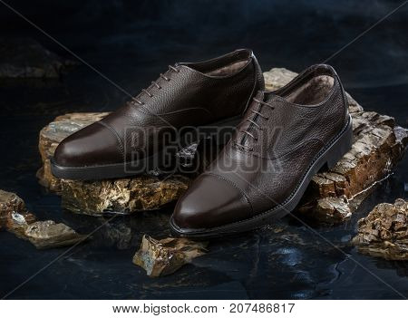 Fashionable men brown shoes for autumn on a dark background