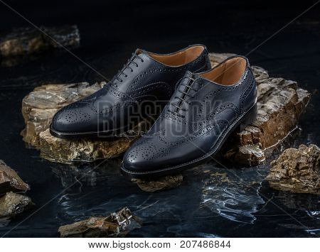 Fashionable men shoes for autumn. Background of stone and water