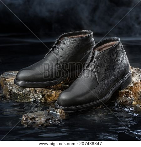 Black leather men boots for cold weather on a black background