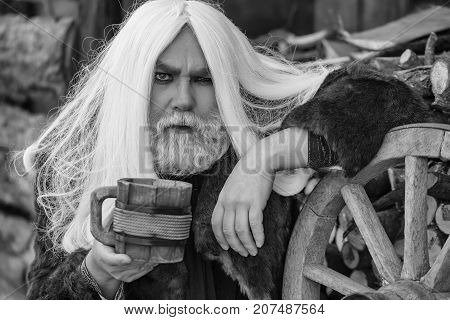 Druid old bearded man with long grey hair and beard in fur coat with wooden mug in hands near wheel outdoor
