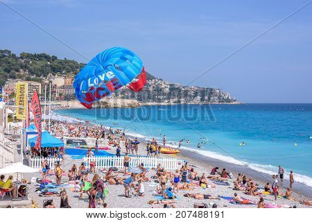 NICE COTE D'AZUR, FRANCE - JUNE 27, 2017: Beautiful daylight view to beach of Nice Cote d'Azur. People relaxing on beach and swimming in water. Parachute man landed on sand.