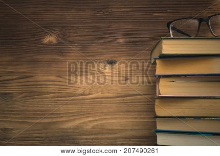 Education. Stacked Books and glasses on wooden wall background with copy space.