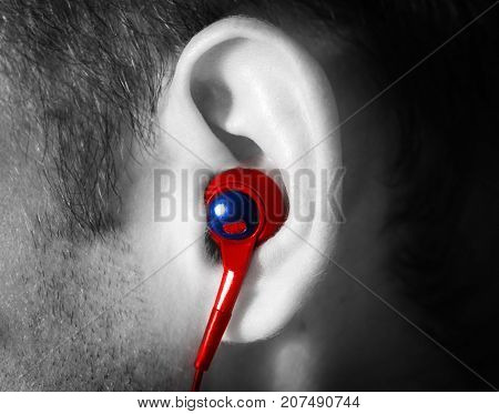 ear man with a red earpiece listens to music