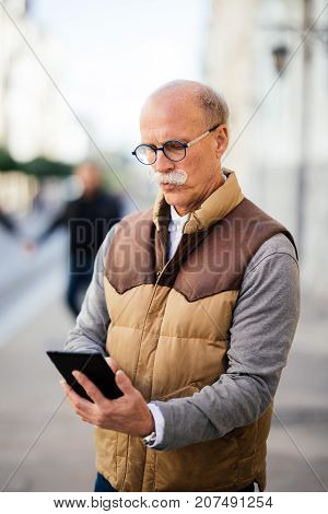 Wireless Technology Keeps My Daily Tasks Streamlined. Shot Of A Senior Man Sitting Outdoors And Look