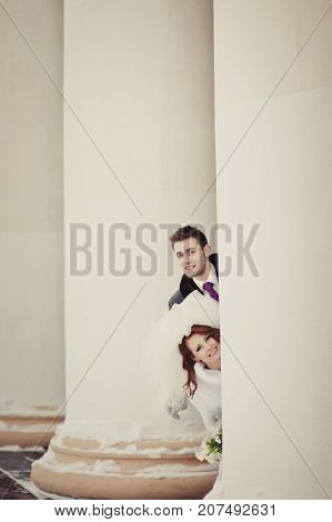 A Beautiful Ginger Bride In A White Fur Coat And Groom Peeking Out From Behind The White Columns. Wi