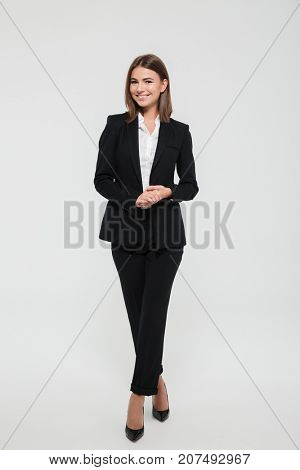 Full length portrait of smiling attractive businesswoman in suit posing while standing with arms crossed and looking at camera isolated over white background