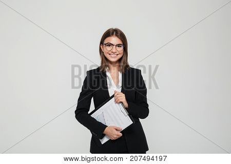 Portrait of a satisfied young businesswoman in suit and eyeglasses holding clipboard with documents and looking at camera isolated over white background