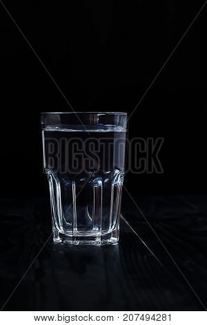 Just a glass of water on a black background on a wooden table.