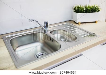 Metal faucet with a stylish sink in the new kitchen. Metal faucet. Faucet in the kitchen. A modern faucet. Faucet with hot and cold water