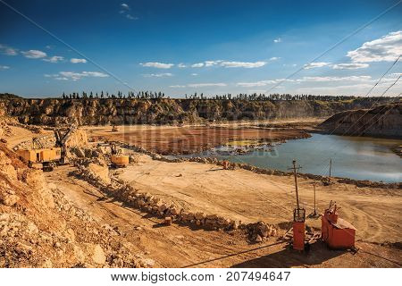 Opencast mining quarry with lots of machinery at work, industrial landscape