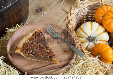 Slice of pecan pie with autumn gourds
